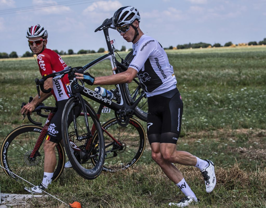 Britain's Chris Froome, right, and Belgium's Jasper De Buyst, left, get back on the road after crashing during the first stage of the Tour de France cycling race over 201 kilometers (124.9 miles) with start in Noirmoutier-en-L'Ile and finish in Fontenay Le-Comte, France, Saturday, July 7, 2018. (Jeff Pachoud, pool photo via AP)